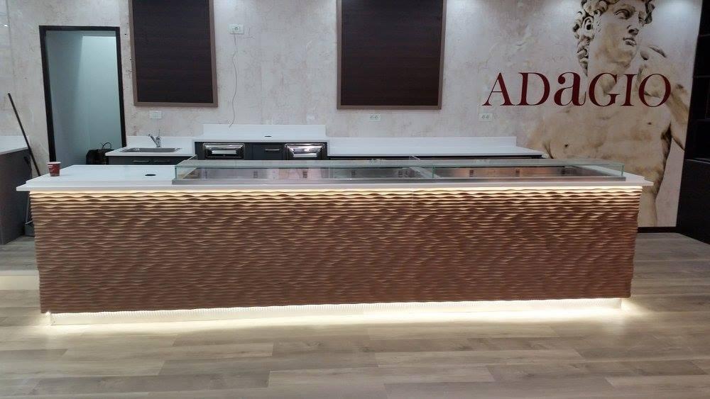 Una cucina con il bancone in legno e luci a effetto onda sul legno e dietro il bancone un raffigurazione del David di Michelangelo e la scritta Adagio