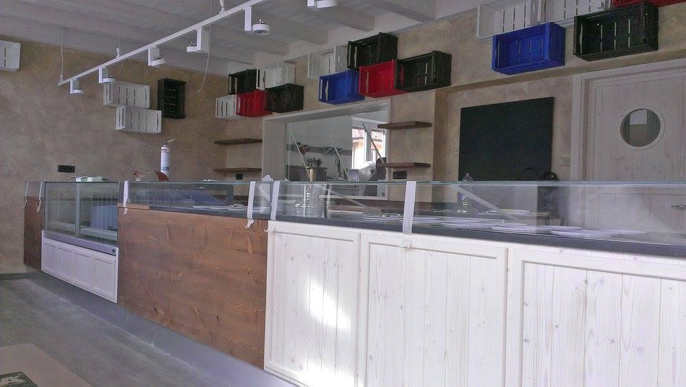 Vista del bancone lungo con vetrine di un ristorante, cassetti della frutta dipinti di  blu, rosso e bianco e fissati al muro come delle mensole