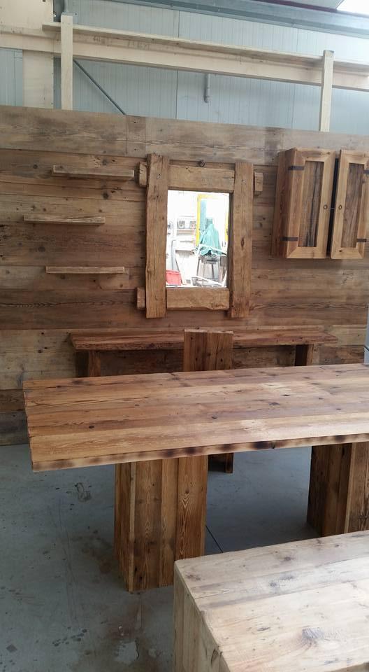 Un mobile con legno scuro con uno specchio in mezzo,  sulla sinistra un mobiletto con delle ante , delle mensole sulla sinistra e una sedia davanti
