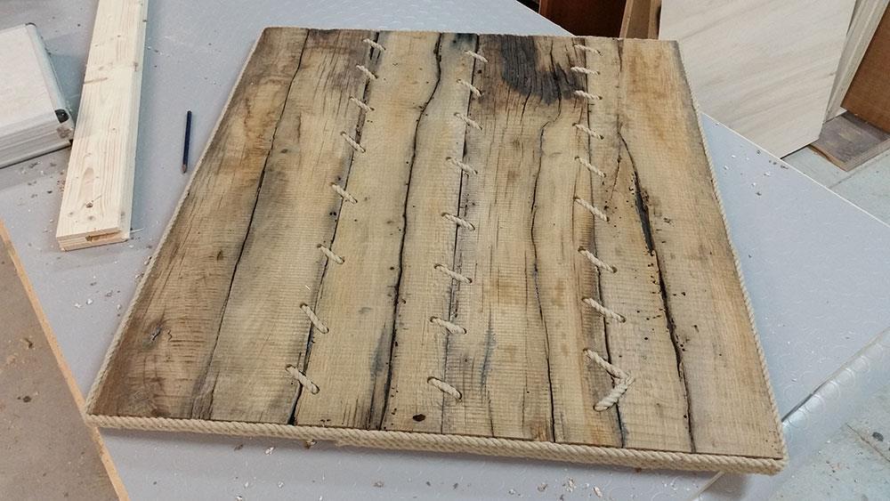 Un quadro di legno realizzato con pezzi di legno antichi legati uno all'altro con un cordino in iuta
