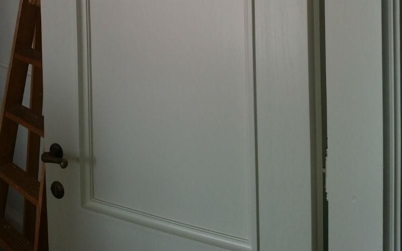 dettaglio di porta bianca e maniglia in ottone