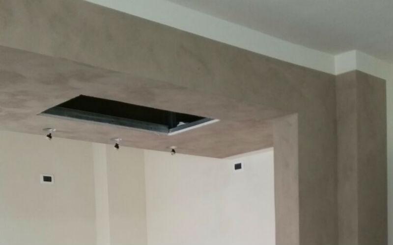 controsoffitto in stanza tinteggiata di bianco e grigio