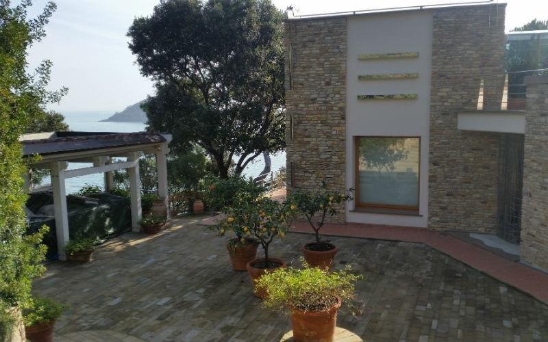 facciata di villa in pietra e verniciatura bianca