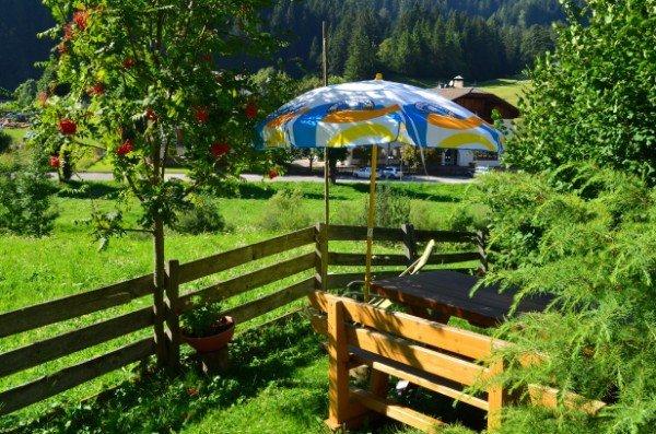 un recinto in legno, un ombrellone e una panchina