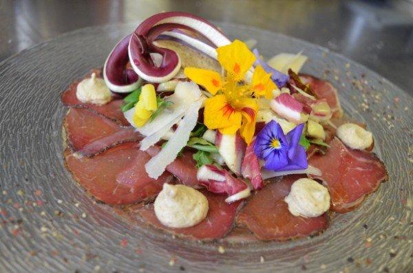 un piatto di salumi, crema , insalata e petali di fiori