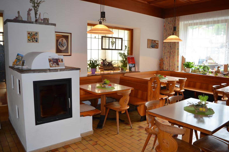 vista interna di un ristorante con tavoli e sedie in legno, forno, infissi con tenda e arredamento