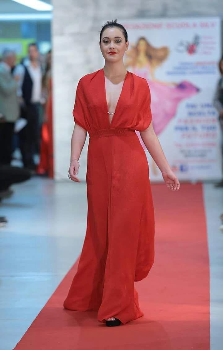 Ragazza sfila con vestito rossastro