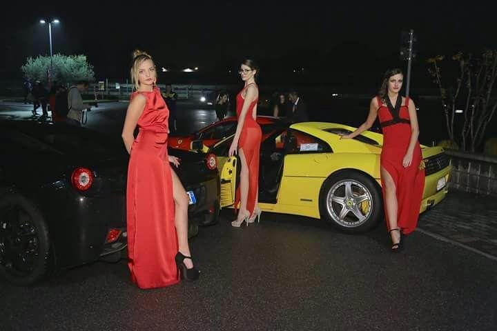 Tre modelle con abito da sera rosso, vicine a macchina gialla