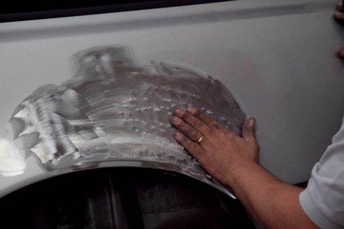 carrozziere rimuove vernice da un'auto