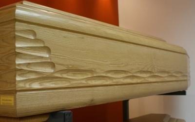 una bara in legno chiaro con sopra dei disegni scolpiti