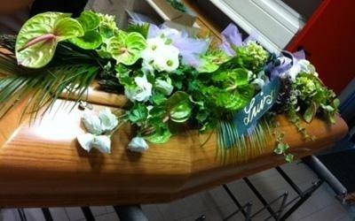 una bara con sopra dei fiori e dei nastri