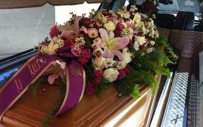 una lapide con sopra un bouquet di fiori e dei nastri con dei nomi scritti