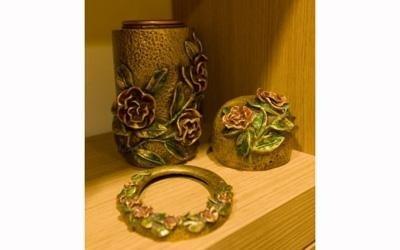 un'urna dorata con sopra dei disegni di alcune rose