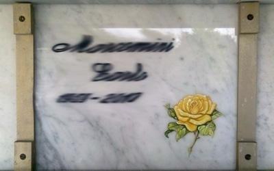 una lapide in marmo con sopra un nome scritto e un disegno di una rosa gialla