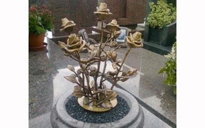 un vaso in marmo con sopra delle rose dorate