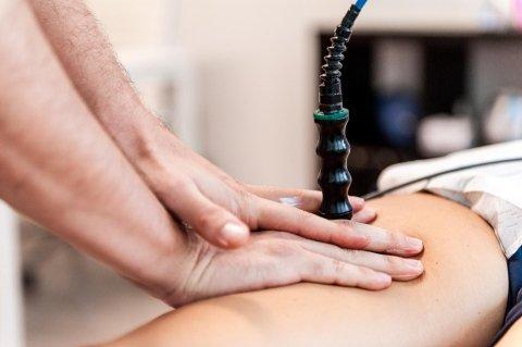 mani di un medico che spingono la coscia di un paziente utilizzando  la tecnica TECAR