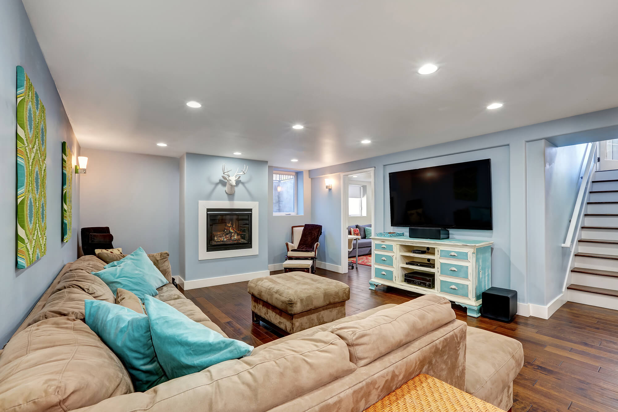 Pastel blue walls in basement living room interior. Large corner sofa with blue pillows and ottoman. Vintage white and blue TV cabinet.