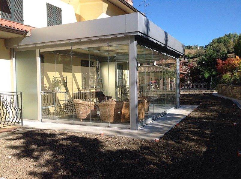 una veranda in vetro vista da lontano con divanetti di paglia, dietro si nota il paesaggio con degli alberi e una ringhiera
