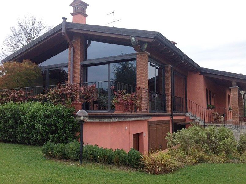 una villa color rosa con tetto e comignolo marrone scuro e di fronte un giardino con delle piante