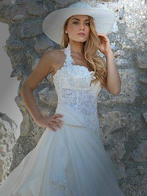 Una modella con un abito e un cappello di color bianco