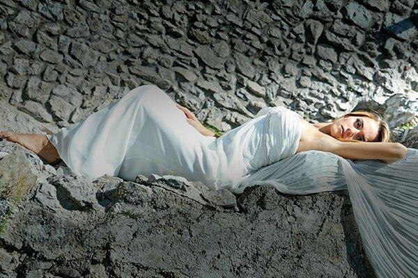 Una donna con un abito lungo di color bianco sdraiata sulle rocce