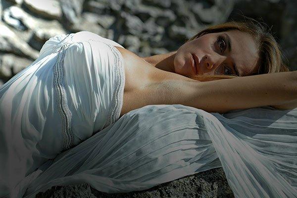 Una donna sdraiata con un abito di color bianco