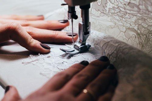 due mani che tengono una stoffa ricamata e un ago di una macchina da cucire