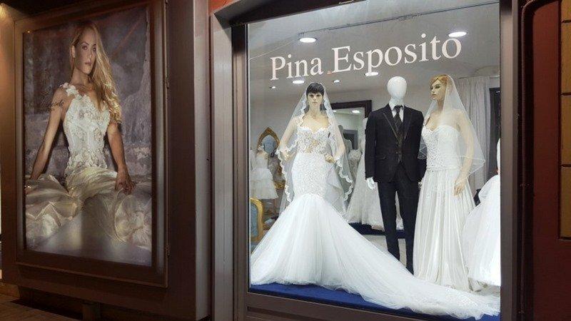 una vetrina con dei manichini con degli abiti nuziali e la scritta Pina Esposito