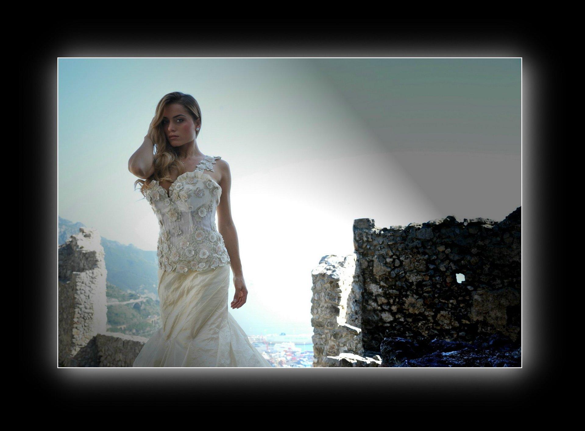 una modella vestita da sposa con cielo di spalle