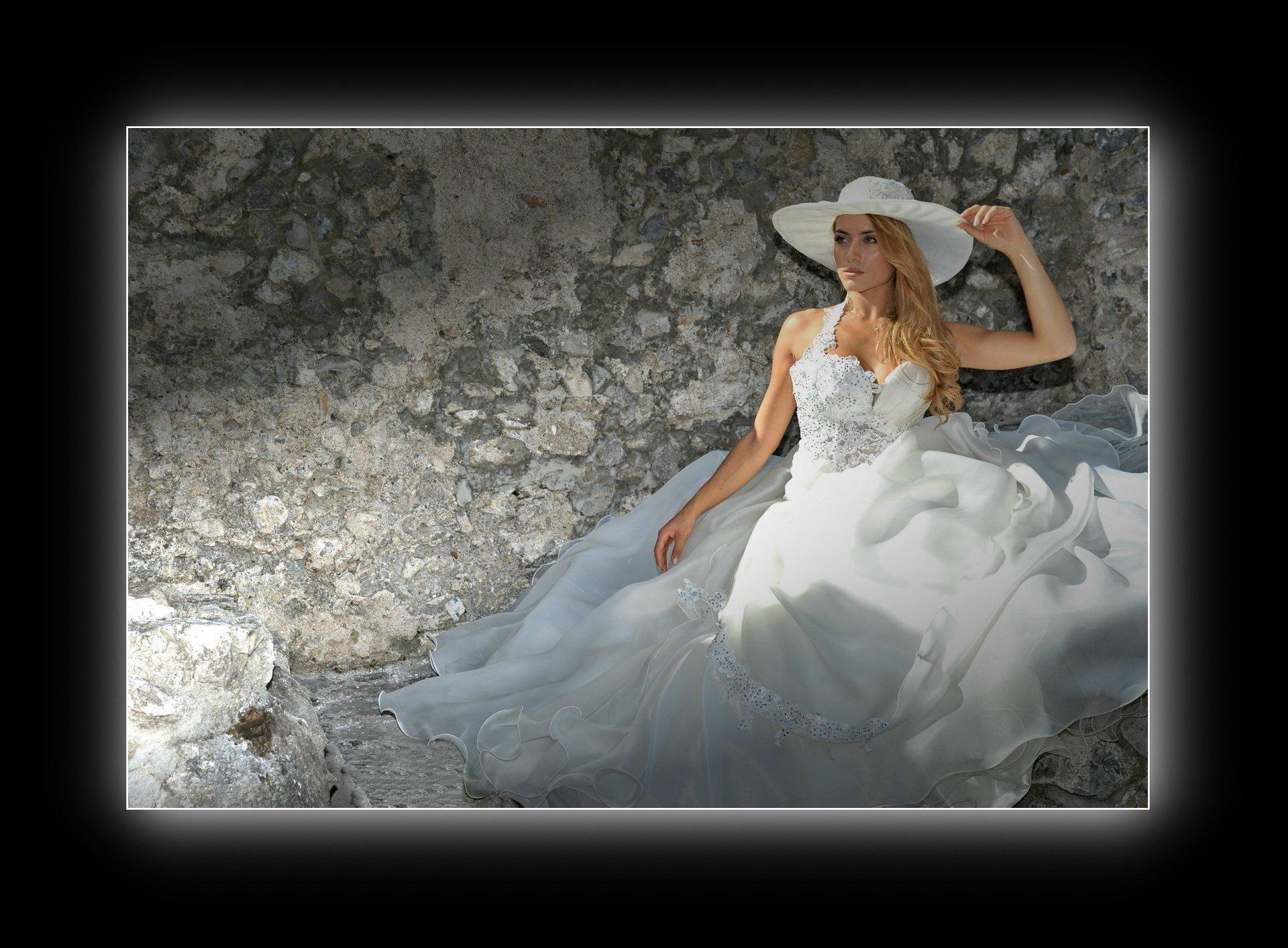 sposa con cappello e muro di spalle