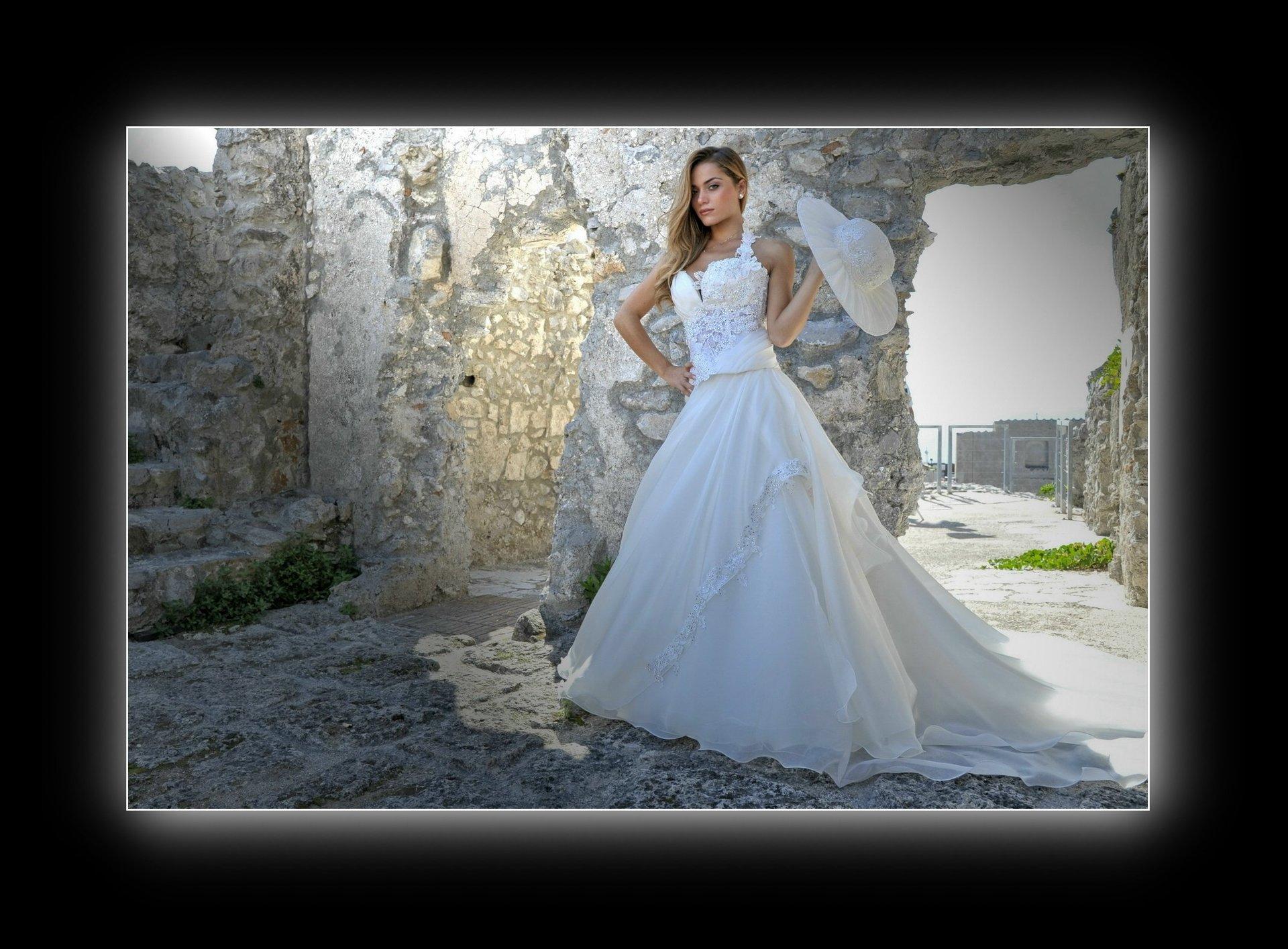 una ragazza in posa vestita da sposa e con cappello