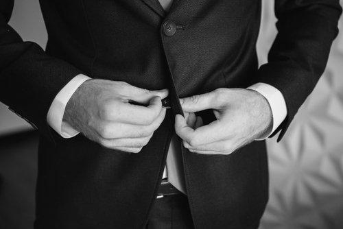 uno sposo che si abbottona la giacca