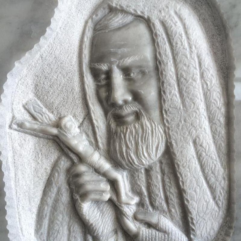 Evidenza di un anziano in marmo bianco con un crocifisso in mano