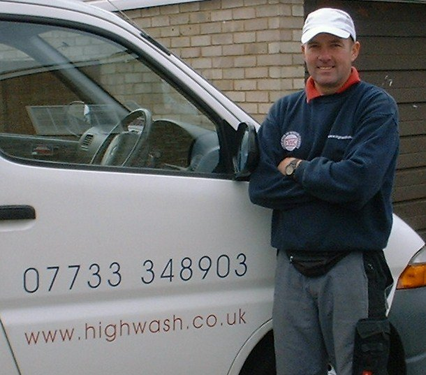 highwash employee standing next to the company cars