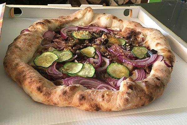 una pizza bianca con cipolle e zucchine