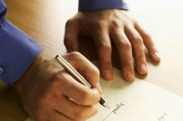 man signing a family law business partnership document in Anchorage, AK