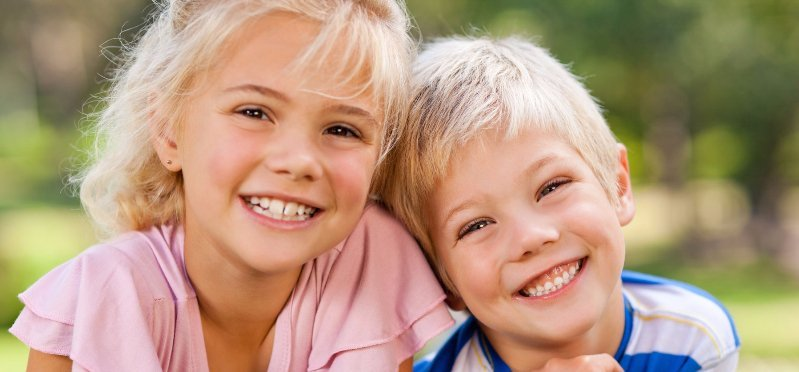un bambino e una bambina con i capelli biondi mentre sorridono