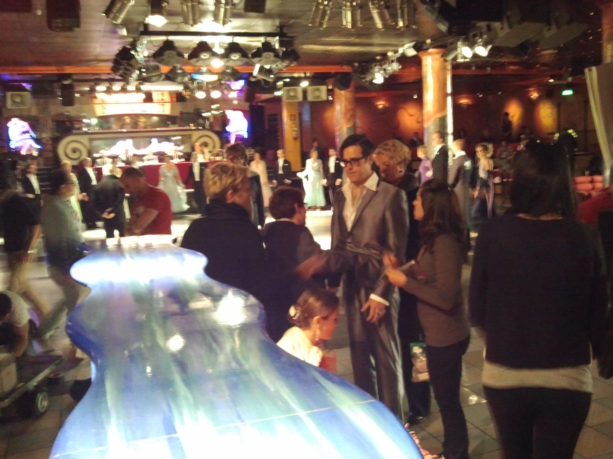 foto leggermente sfuocata dell' interno del locale con delle persone in piedi e un bancone di vetro