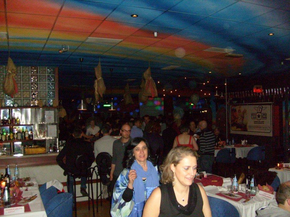 delle persone in piedi e sedute all'interno del club con sul soffitto delle luci effetto arcobaleno