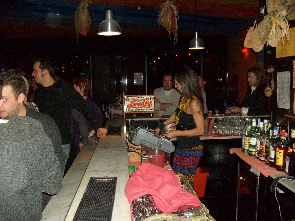 delle persone vicino al bancone del bar e una barista vicino alla cassa mentre sta versando un cocktail in un bicchiere