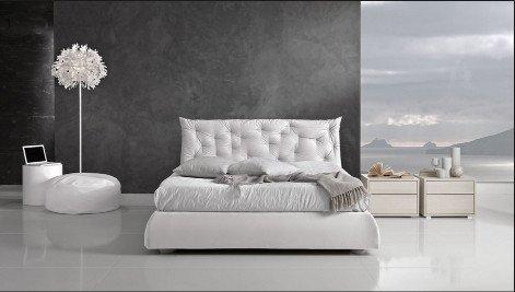 un letto di color bianco e sulla destra due comodini