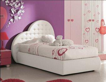 un letto singolo di color bianco con la testata a forma di un cuore