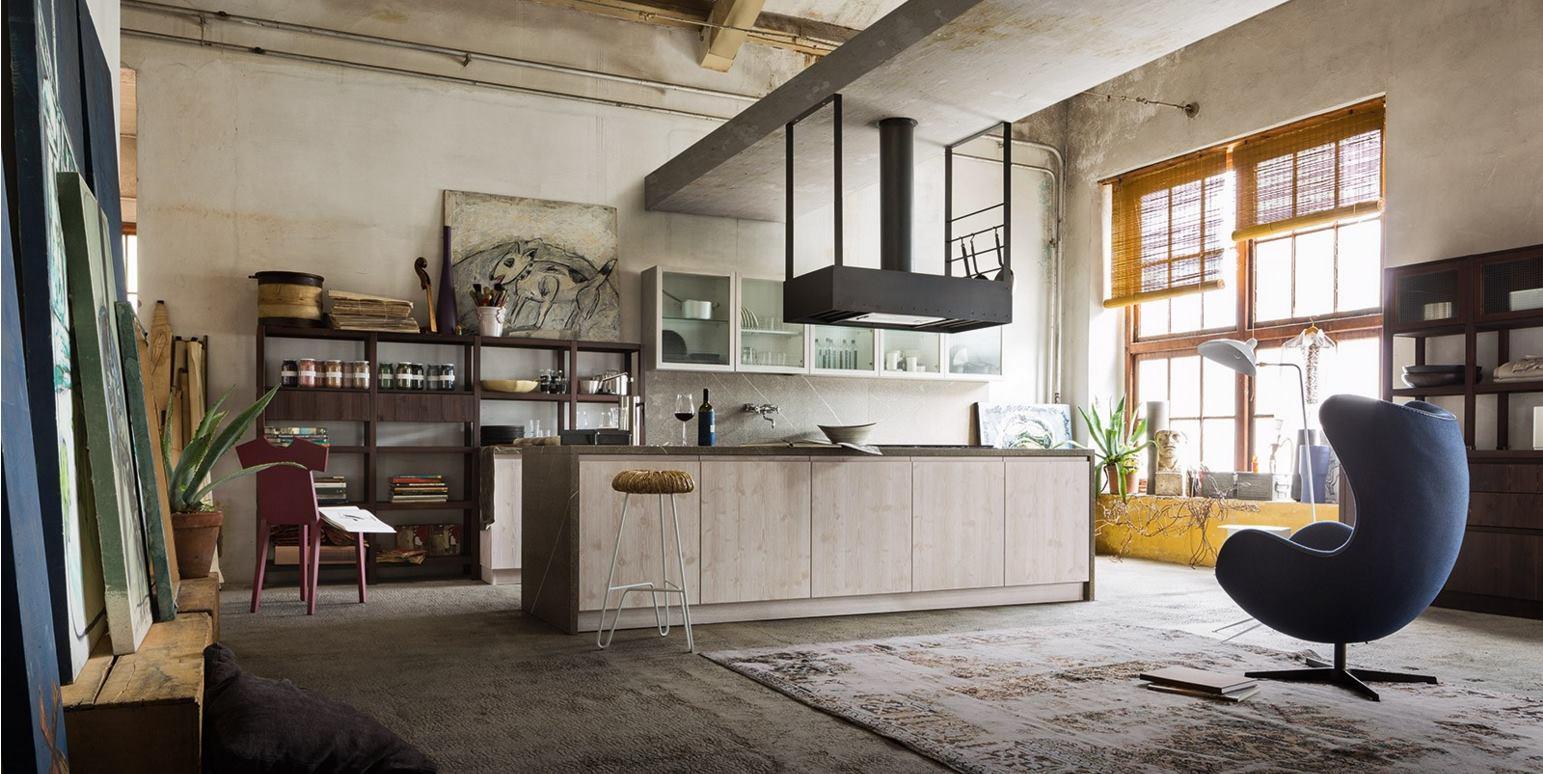 una cucina con una penisola e degli scaffali in legno e davanti una poltrona di color blu