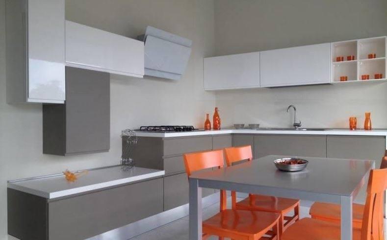 una cucina con dei mobili di color bianco, grigio e le sedie di color arancione