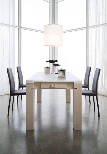 un tavolo allungabile con quattro sedie di color nero