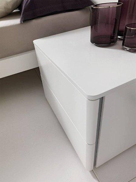 un comodino di color bianco con due cassetti e due vasi sopra