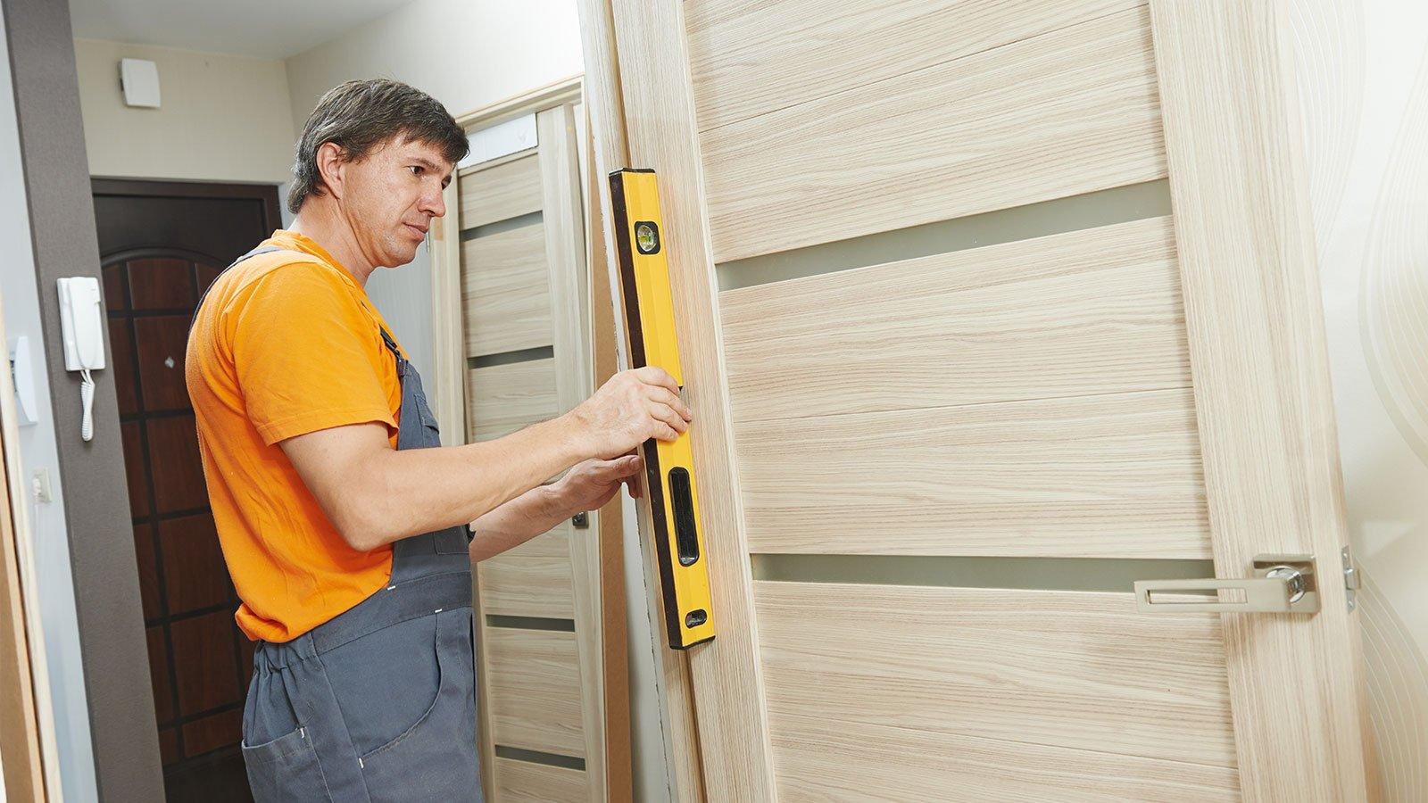 un uomo con una livella mentre misura  una porta di legno