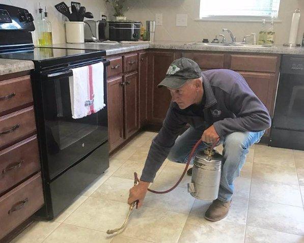 Worker spraying pesticides on wooden drawer