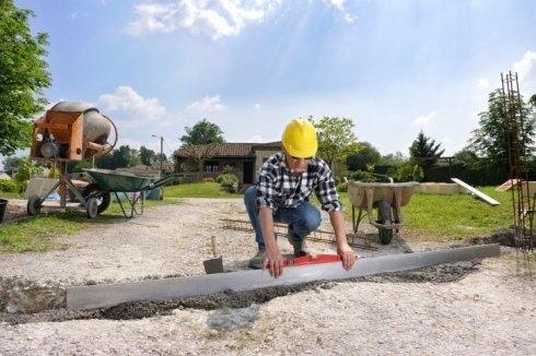 operaio fissa una lamiera di metallo su una strada non asfaltata