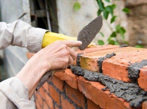 muratore mentre costruisce una parete di cemento con dei mattoni